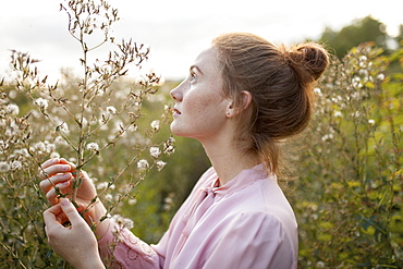 Russia, Omsk, Young woman in meadow