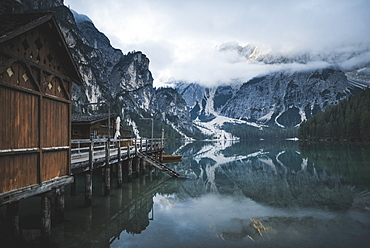 Italy, Wooden houses and pier at Pragser Wildsee in Dolomites