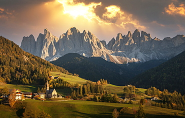 Italy, Santa Maddalena, Val di Funes (Funes Valley), Trentino-Alto Adige Region, Mountain range overlooking green valley at sunset