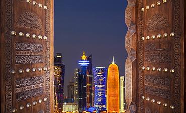 Qatar, Doha, Modern buildings seen through old door