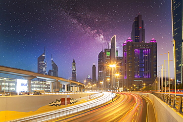 United Arab Emirates, Dubai, Traffic on highway and modern city architecture at dusk
