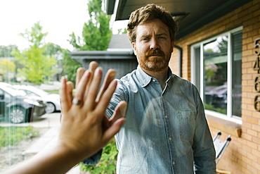 USA, Utah, Salt Lake City, Wife and husband touching hands through window
