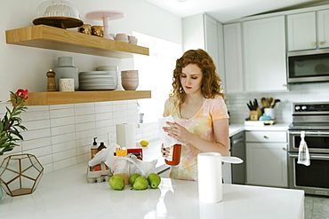 Woman cleaning jar in kitchen