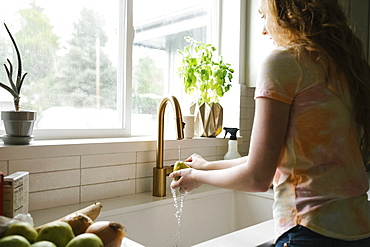 Woman washing pear in kitchen