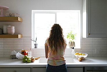 Woman washing fruit and vegetables in kitchen