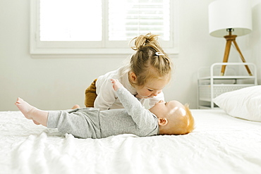 Toddler sister embracing her baby brother on bed