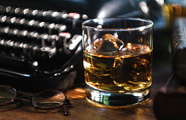 Whiskey glass next to typewriter on desk