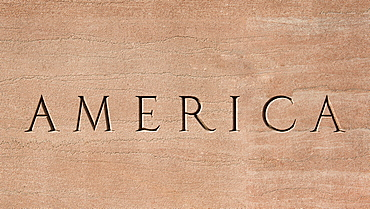 Word America engraved into stone surface