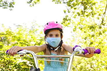 Girl (6-7) wearing flu mask and riding bicycle