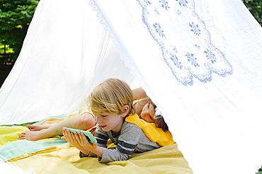 Girl (6-7) and boy (4-5) relaxing in homemade tent in backyard