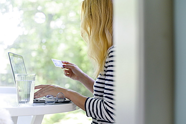 Woman using laptop and credit card