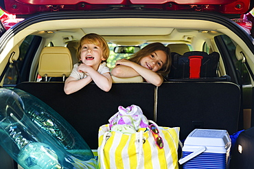 Boy (4-5) and girl (6-7) sitting in car ready for vacation trip