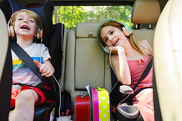Boy (4-5) and girl (6-7) listening to music in car