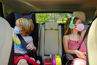 Masked boy (4-5) and girl (6-7) listening to music in car