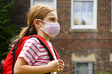 Schoolgirl (6-7) wearing flu mask