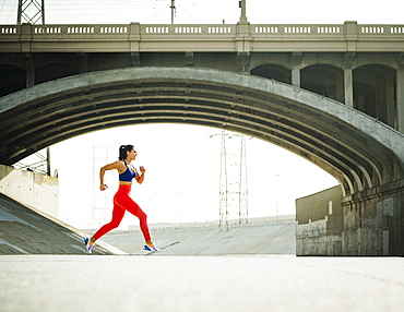 USA, California, Los Angeles, Sporty woman jogging in urban setting