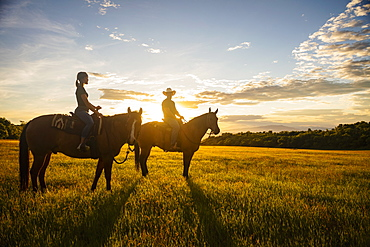 USA, Utah, Salem, Father and daughter (14-15) riding horses at sunset