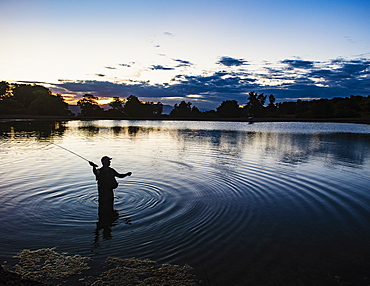 USA, Utah, Salem, Silhouette of man fly fishing in lake at dusk