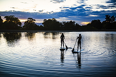 USA, Utah, Salem, Two teenage girls (14-15) on stand up paddle bards on lake at dusk