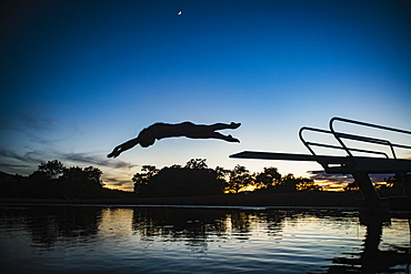 USA, Utah, Salem, Teenage girl (14-15) jumping from pier into lake at dusk