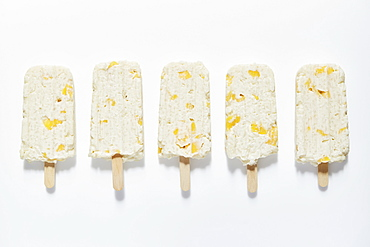 Rice and mango popsicle sticks on white background