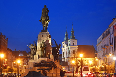 Poland, Lesser Poland, Krakow, Monument with statues on illuminated old town square