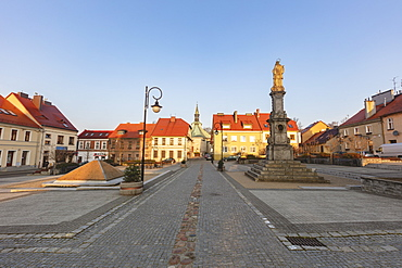 Poland, Opole, Toszek, Historic town square with statue at dusk