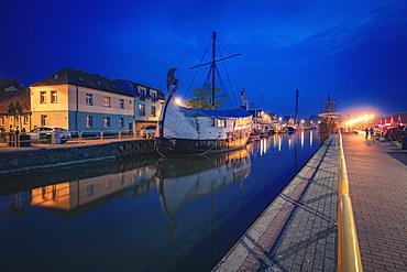 Poland, Pomerania, Leba, Historic ship moored in harbour at night