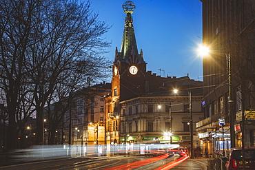 Poland, Lesser Poland, Krakow, Illuminated city street with clock tower at night