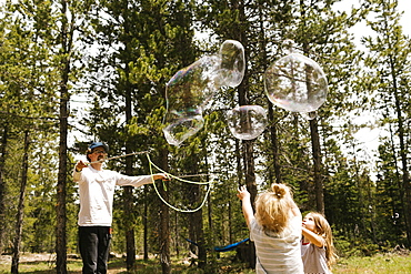Father making large soap bubbles in forest for two daughters (2-3, 4-5), Wasatch-Cache National Forest
