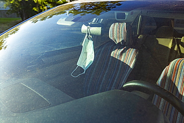 Face mask hanging from rear view mirror inside car