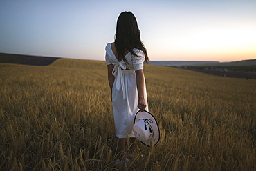 France, Woman in white dress standing in field