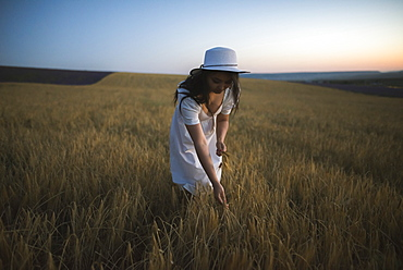 France, Woman in white dress and hat in field
