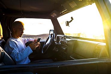 Teenager (16-17) in car using smartphone