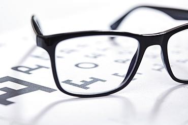 Close up of eyeglasses on eye chart