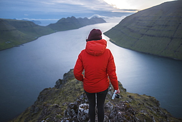Denmark, Faroe Islands, Gjgv, Woman standing on Klakkur mountain and looking at fjord