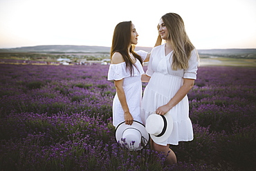 France, Young couple in white dresses standing in lavender field