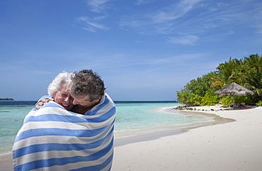 Indian Ocean, Maldives, Ari Atoll, Vilamendhoo Island, Happy couple wrapped in striped beach towel on tropical beach