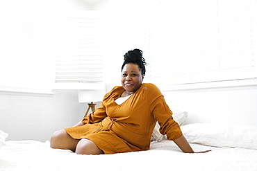 Portrait of smiling woman in orange dress sitting on bed