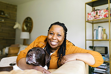 Portrait of smiling woman sitting on sofa with dog