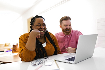 Smiling man and woman looking at laptop at desk in home office