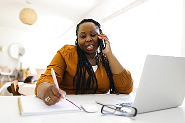 Woman working at desk at home, writing and talking on mobile phone