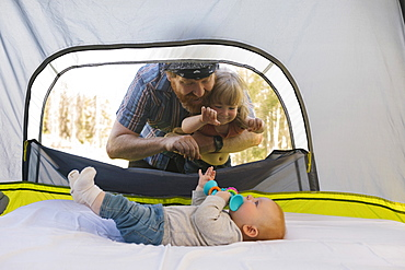USA, Utah, Uinta National Park, Father and daughter (2-3) peeking into tent and looking at baby boy (6-11 months) inside