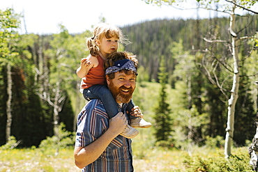 USA, Utah, Uinta National Park, Portrait of smiling man carrying daughter (2-3) on shoulders in landscape