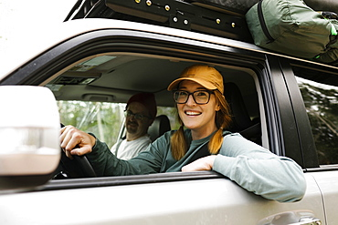 Woman and man sitting in off road car with tent on roof