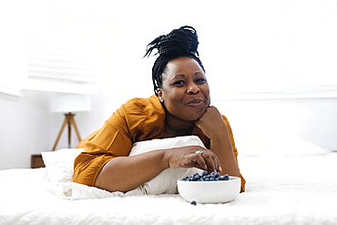 Woman lying on bed, eating blueberries and watching tv