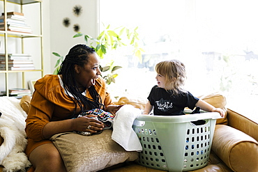 Woman playing with little girl (2-3) sitting in laundry basket