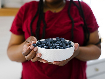 Close up of woman holding bowl with blueberries
