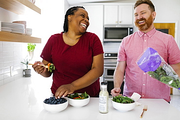 Happy man and woman preparing salad in kitchen