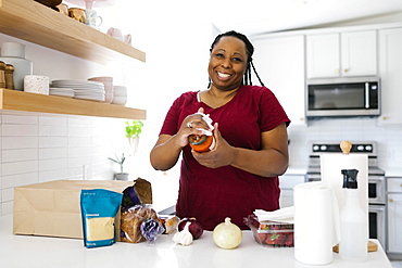 Portrait of smiling woman disinfecting food in kitchen